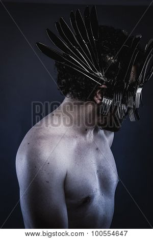 Chef, naked man with a crown of forks and knives in the head, concept designer kitchen