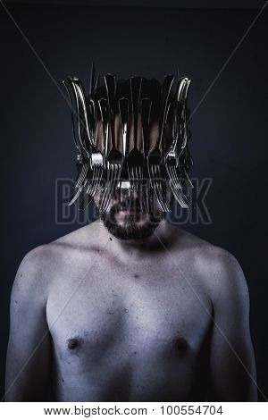 naked man with a crown of forks and knives in the head, king of the kitchen