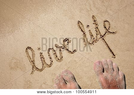 Concept or conceptual live life text handwritten in sand on a beach with feet