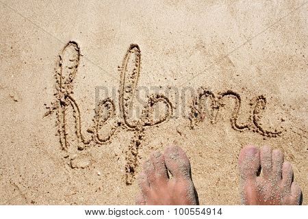 Concept or conceptual help text handwritten in sand on a beach in an exotic island background with feet
