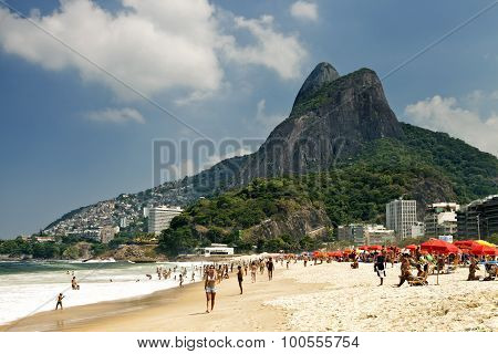 People are relaxing sunbathing walking playing in the sea on Ipanema beach in Rio de Janeiro on a h