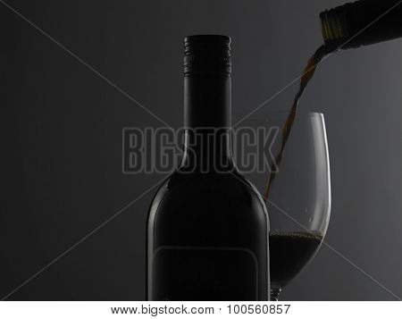 Elegant wine bottle and wine glass in a black background