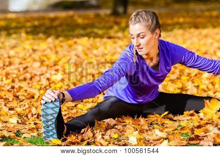 Woman doing gymnastics in autumn foliage