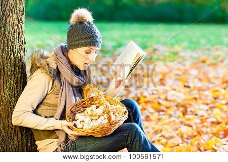 Woman reading book on mushroom foray