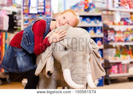 Little girl in toy store cuddling with stuffed animal, shelves with toys in the background