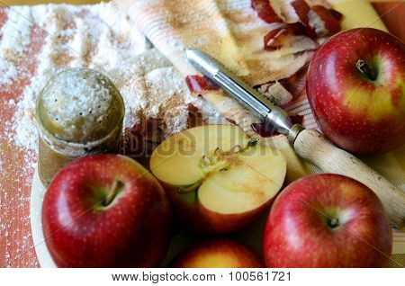 Apples, peeler,  sugar dispenser and tea towel
