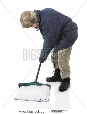 Full length image of a bundled senior man scooping up a shovelful of snow.  On a white background.
