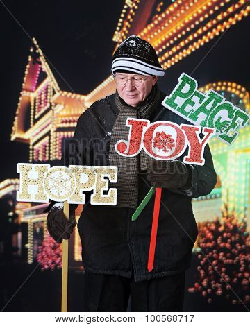 A senior man putting out Christmas yard signs at night in front of his decorated house.  The signs, in red, green and gold say
