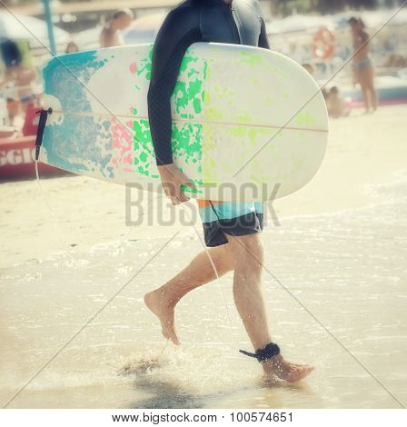 Surfer With Longboard On The Beach