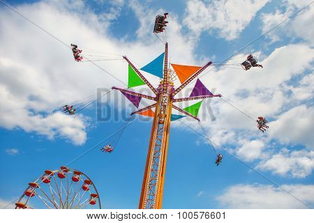 Rides at a county fair. Focus on ride, people in swings have motion blur.