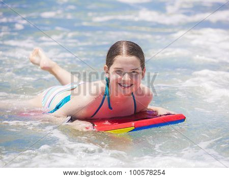Cute young teenager smiling with braces while on a boogie board and playing in the ocean waves