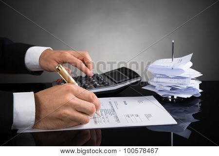 Businessperson Calculating Invoice At Desk