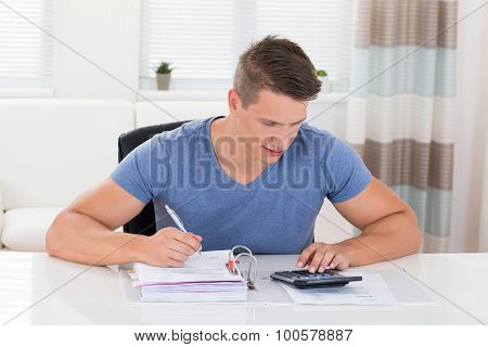 Young Man Calculating Invoice