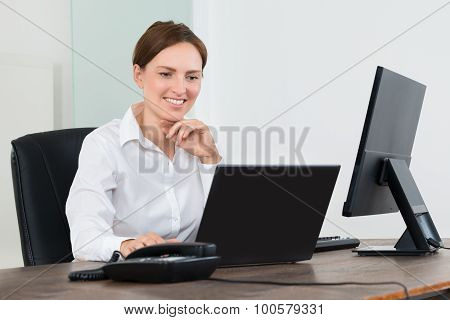 Businesswoman Working On Laptop And Desktop Computer