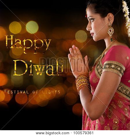 Indian woman in traditional sari praying and celebrating Diwali or deepavali, fesitval of lights at temple. Girl prayer hands folded, beautiful lights bokeh background.
