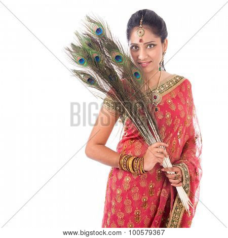 Portrait of beautiful Indian woman holding peacock feathers, isolated on white background.