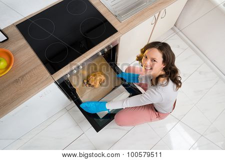 Woman Putting Chicken In Oven