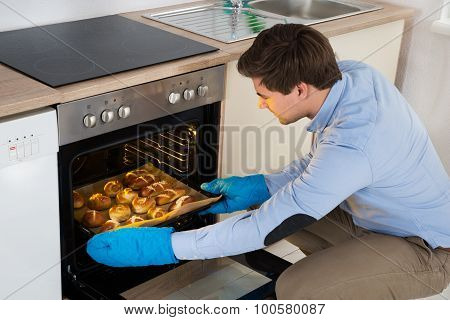 Man Taking Baked Bread From Oven