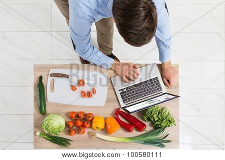 Man With Laptop In Kitchen