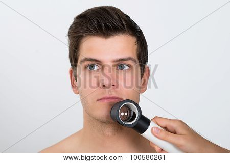 Person Examining Man Face With Dermatoscope