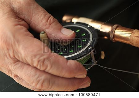 Man with hand on fishing reel