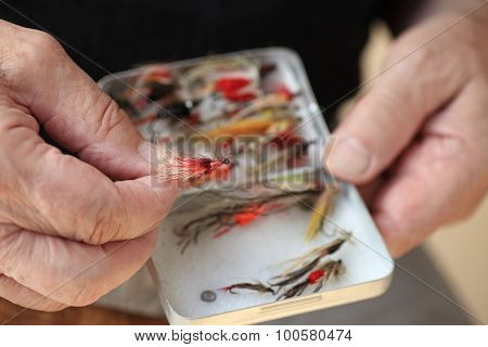 Man with his collection of artificial fishing flies