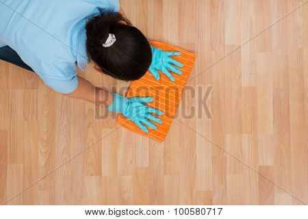 Woman Rubbing Wooden Floor With Cloth