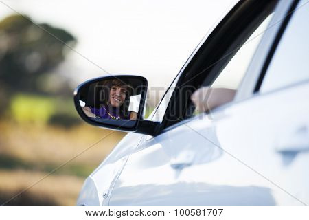 Beautiful woman face reflected on the side mirror of her new car