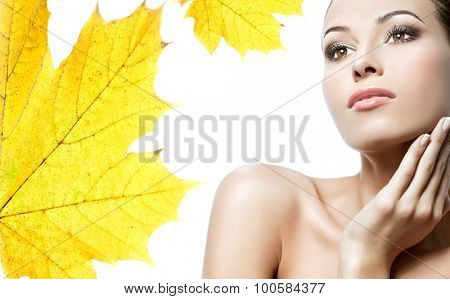 closeup beauty portrait of attractive caucasian young woman brunette isolated on white studio shot lips face head and shoulders yellow maple leaf autumn