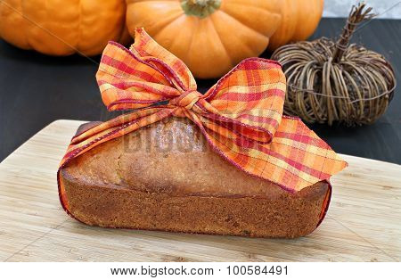 Pound Cake With A Fall Ribbon In A Fall Setting.