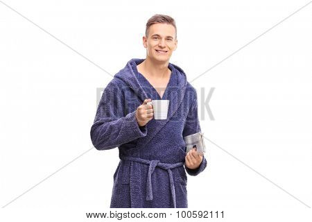 Relaxed young man in a bathrobe holding a cup of coffee and a newspaper isolated on white background