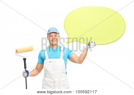 Confident young house decorator in a white jumpsuit holding a paint roller and a big yellow speech bubble isolated on white background