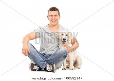 Young man sitting on the floor and hugging a Labrador puppy isolated on white background