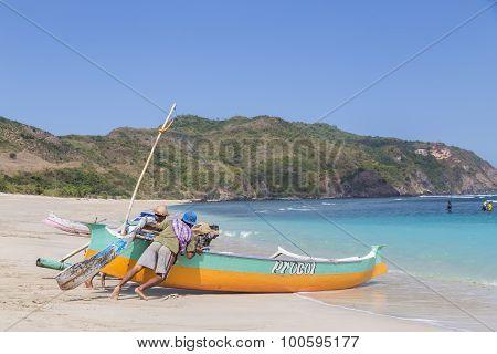 Two fishermen pushing a boat