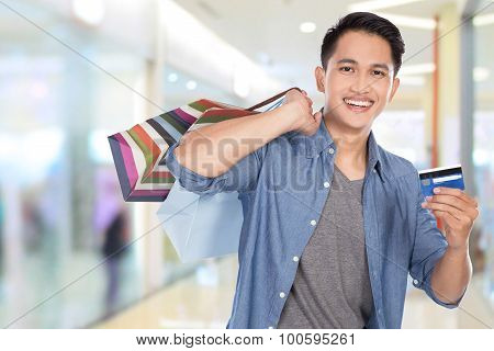 Young Asian Man Holding Shopping Bags And Credit Card, Close Up