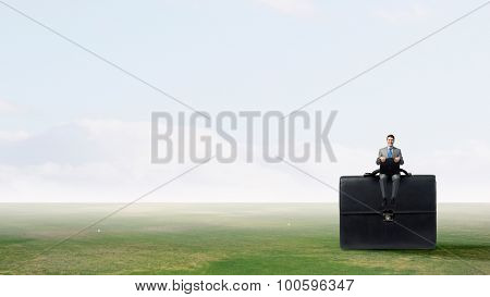 Young smiling businessman sitting on giant briefcase
