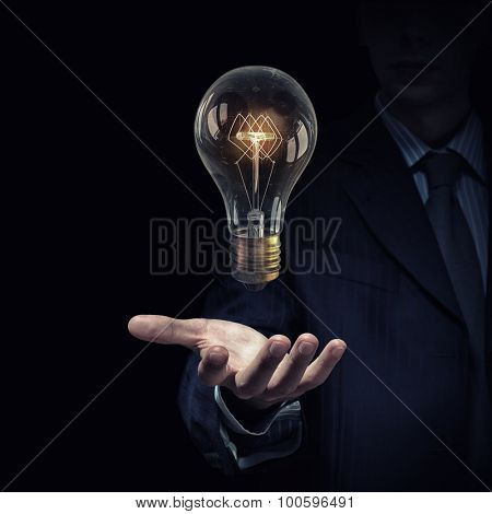 Close up of human hand holding glass glowing light bulb