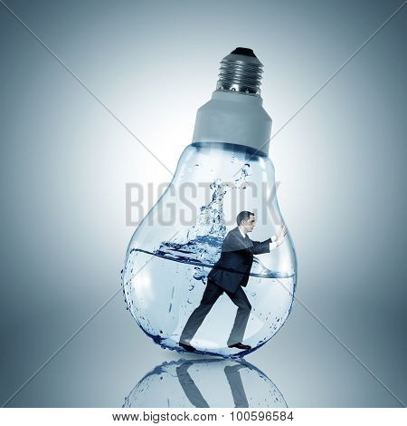 Businessman inside light bulb with water trying to get out