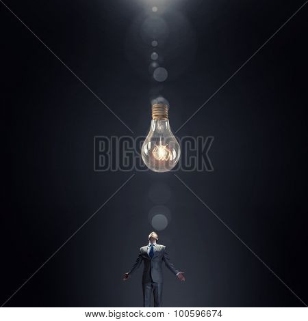 Young businessman and glass glowing light bulb