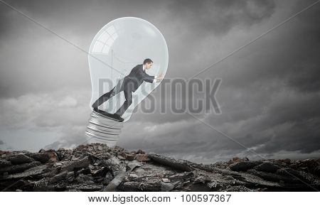 Businessman inside light bulb trying to get out
