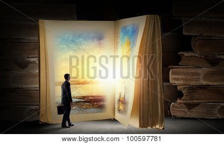 Big old opened book and miniature of businessman
