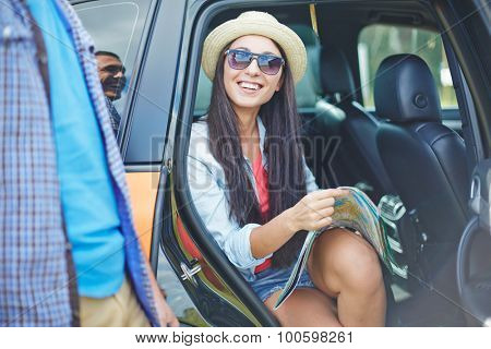 Female traveler with map sitting in car and looking at her boyfriend