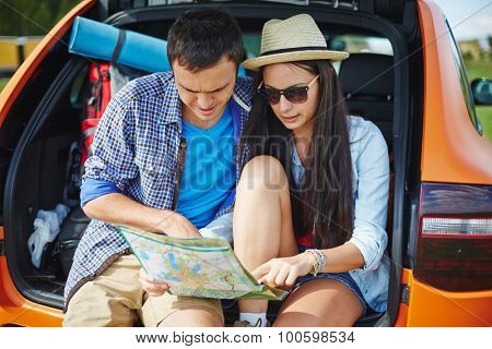 Young couple looking at map while choosing their travel route
