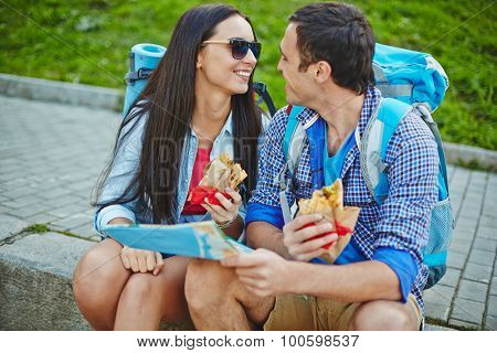 Young couple with backpacks having snack in urban environment