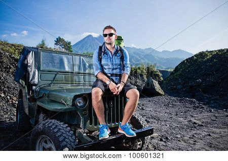 Handsome Young Caucasian Man Sitting On The Hood Of An Offroad Car, Mountains Background
