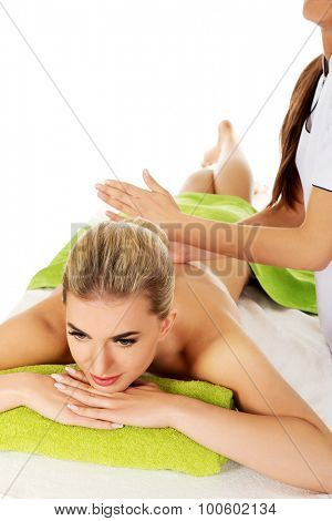 Young woman is being massaged, isolated on white.
