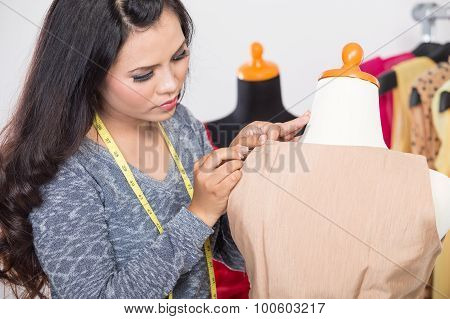 Fashion Designer Or Tailor Working On A Design Or Draft, Measuring On A Dressmakers Dummy