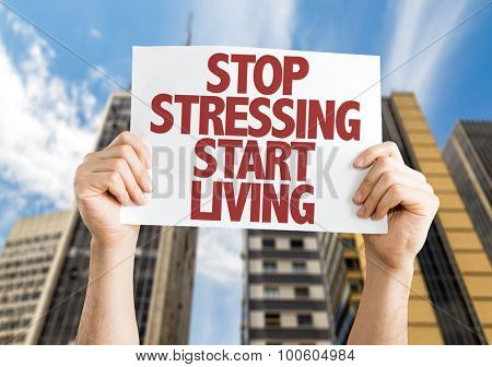 Stop Stressing Start Living placard with cityscape background