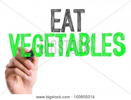 Hand with marker writing the word Eat Vegetables