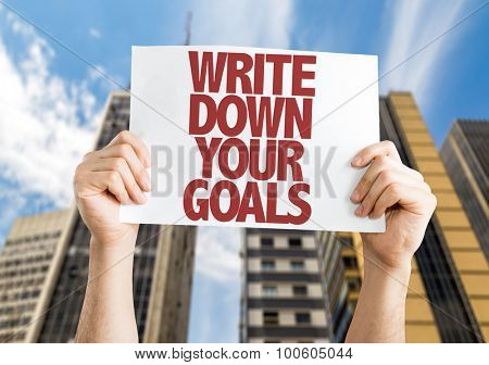 Write Down Your Goals placard with cityscape background